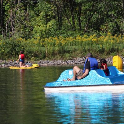 A kayack, paddle boat, and inflatable boat in Pine Hill Lake at the Belleayre Beach